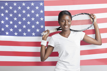 Portrait of young woman with tennis racket against American flag