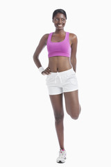 Young African American woman exercising over white background