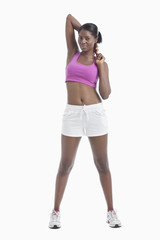 Portrait of young woman stretching arms over white background