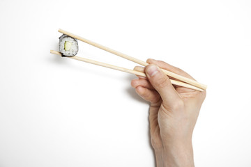 Man's hand holding sushi roll in chopsticks against white background
