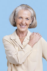 Portrait of smiling senior woman in casuals with hand on shoulder against blue background