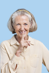 Portrait of smiling senior woman in casuals with finger on lips against blue background