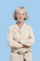 Portrait of smiling senior woman in casuals with arms crossed against blue background