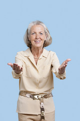 Portrait of smiling senior woman in casuals gesturing against blue background