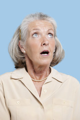 Shocked senior woman in casuals looking away against blue background