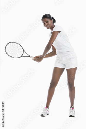 Portrait of young woman with tennis racket standing over white background
