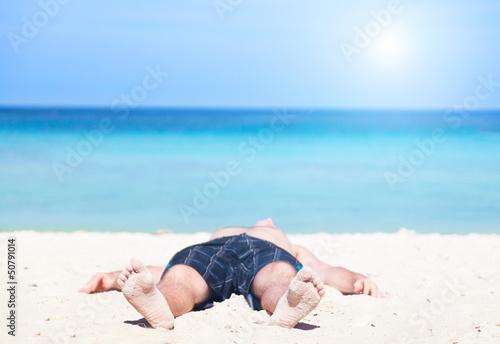 man lies on a peschchany beach on an ocean coast