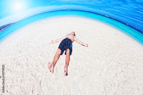 man lies on a peschchany beach on an ocean coast