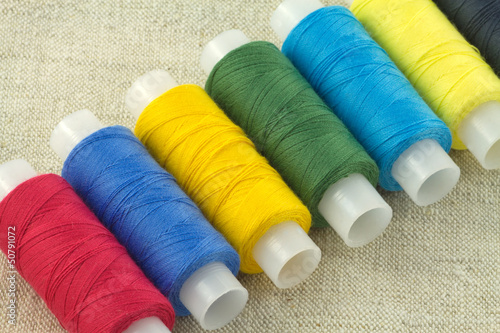 Row of of color threads spools on beige fabric close up