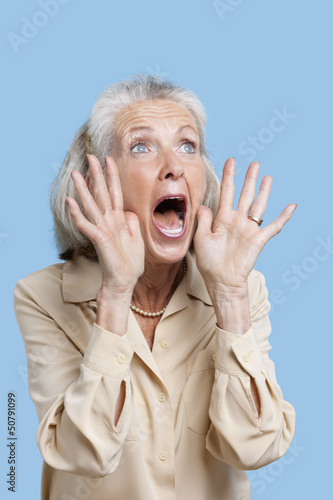 Frightened senior woman screaming against blue background