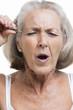 Senior woman tweezing eyebrows against white background