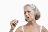 Worried senior woman checking thermometer against white background