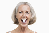 Portrait of senior woman with pill between her teeth against white background
