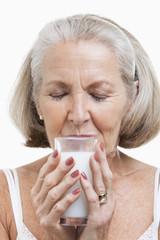 Senior woman drinking milk against white background
