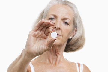 Portrait of senior woman holding a pill against white background