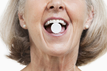Senior woman with a pill between her teeth against white background
