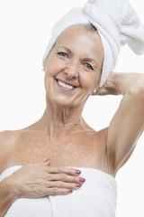 Portrait of senior woman wrapped in towels against white background