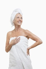 Smiling senior woman wrapped in towels against white background