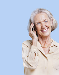 Smiling senior woman using cell phone against blue background