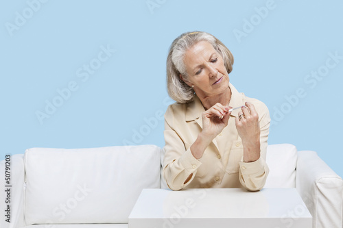 Senior woman filing nails at home