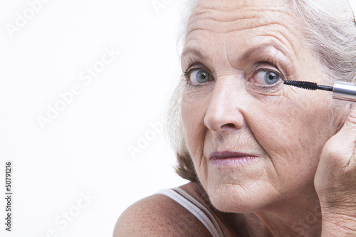 Senior woman applying mascara