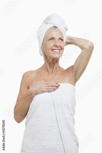 Senior woman wrapped in towels against white background