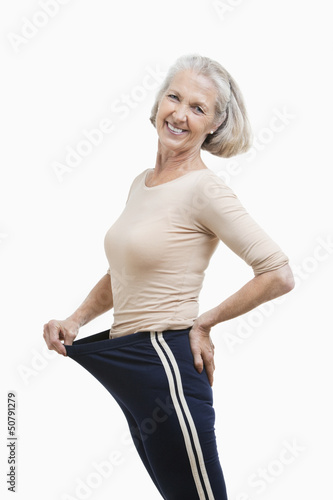 Portrait of senior woman in oversized pants against white background