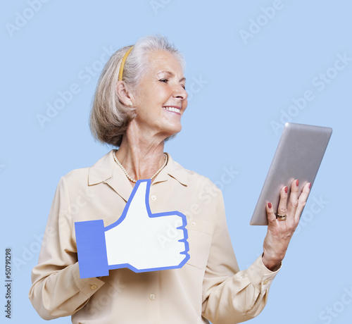 Senior woman with tablet PC holding fake like button against blue background