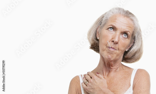 Unwell senior woman with thermometer in mouth against white background