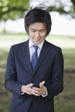 Young businessman using cell phone at park