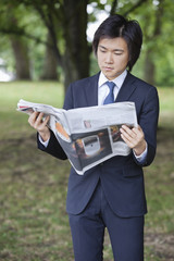 Young businessman reading newspaper at park