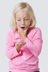 Shocked young girl holding coins over white background