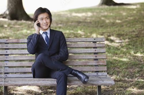 Young businessman using cell phone while sitting on bench at park