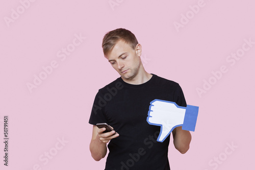 Young man with cell phone holding fake dislike button against pink background