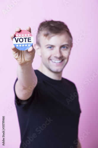 Portrait of a young man holding a VOTE badge up to the camera against pink background