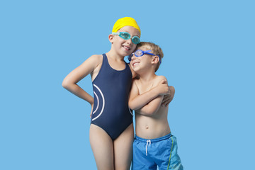 Happy young siblings in swimwear with arm around over blue background