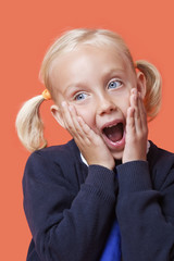 Surprised young schoolgirl with hands on face over orange background