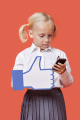 Young schoolgirl with cell phone holding fake like button against orange background