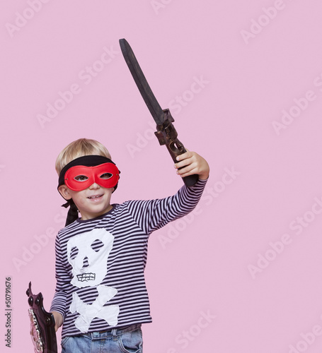 Happy young boy wearing eye mask holding sword and shield over pink background