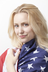 Portrait of beautiful young Caucasian woman wrapped in American flag against white background