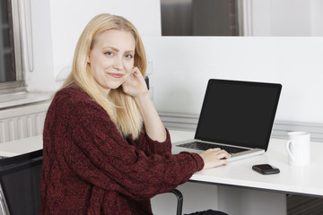 Portrait of happy young businesswoman with laptop sitting at desk in office