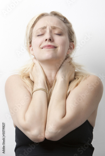 Young Caucasian woman suffering from neckache standing against white background