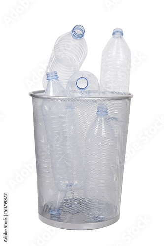 Empty bottles in garbage bin over white background