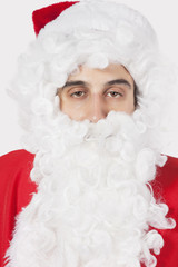 Portrait of young man in Santa costume against gray background