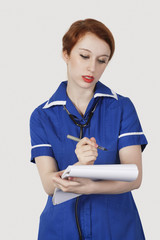 Young female nurse writing on ledger against white background
