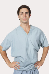 Portrait of confident man in surgical scrubs standing against gray background