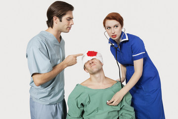 Male doctor with female nurse examining an injured patient against gray background