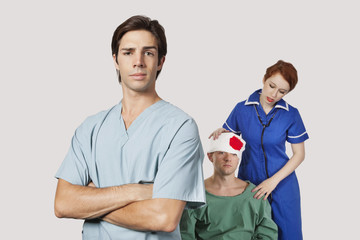 Portrait of male doctor with female nurse treating an injured patient against gray background