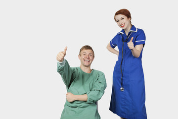 Portrait of young male patient with female nurse gesturing thumbs up against gray background