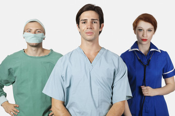 Portrait of three confident medical practitioners against gray background